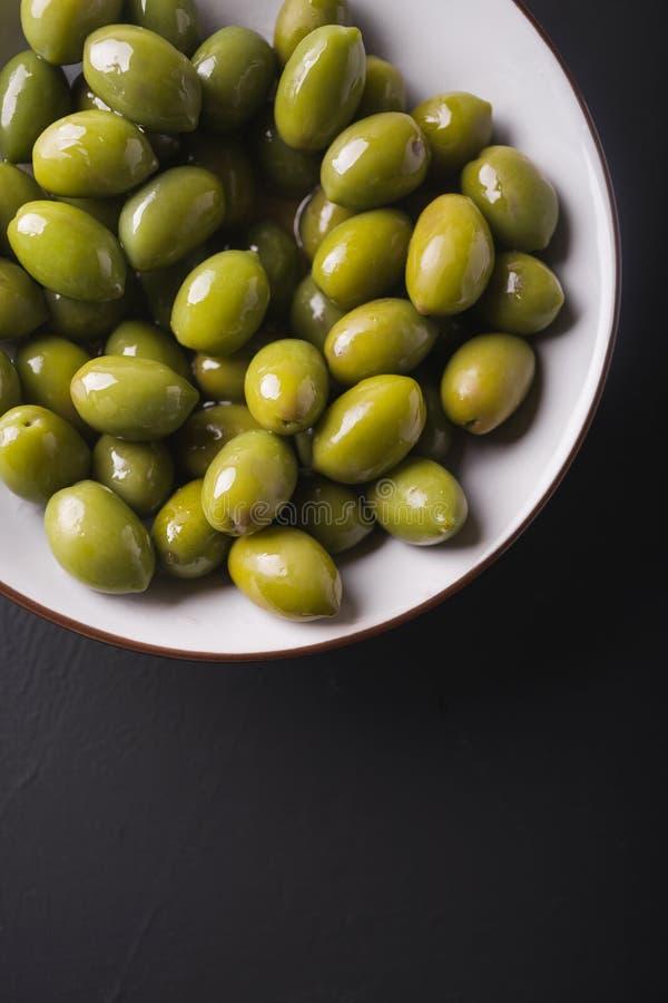 在一个白色碗的绿橄榄在黑背景 库存图片