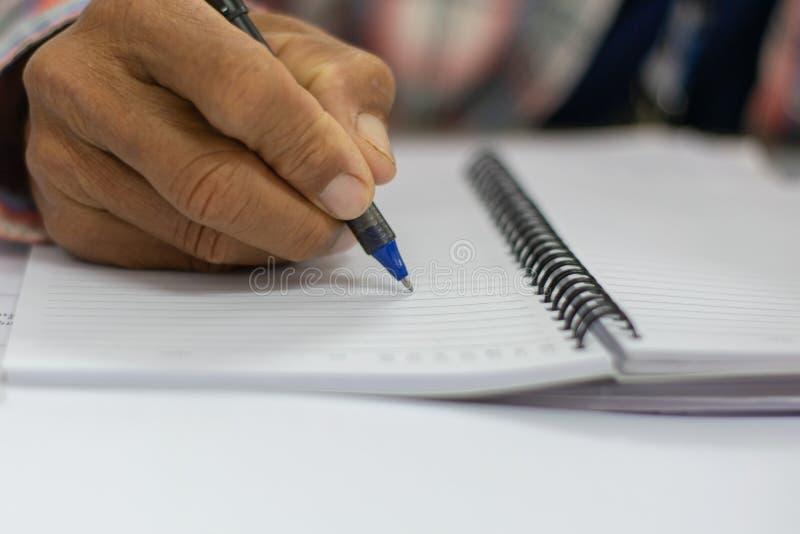在一个白色笔记本的人手写的笔记 免版税库存图片
