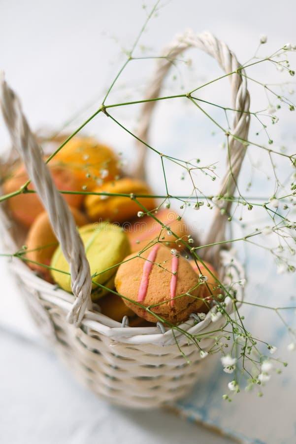 在一个白色篮子的蛋白杏仁饼干在轻的木背景 免版税库存照片