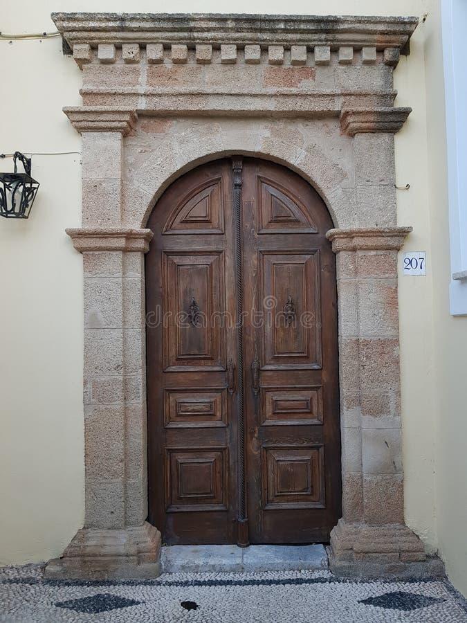 在一个白色老房子的中世纪sentury样式的破旧的木门在一个老greec镇的街道上的 免版税图库摄影