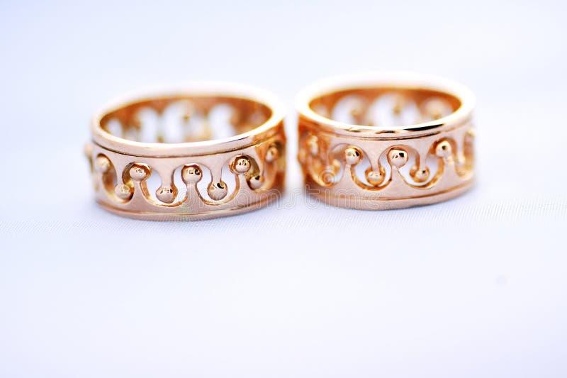 在一个白色背景特写镜头的两个金子婚戒 免版税库存图片