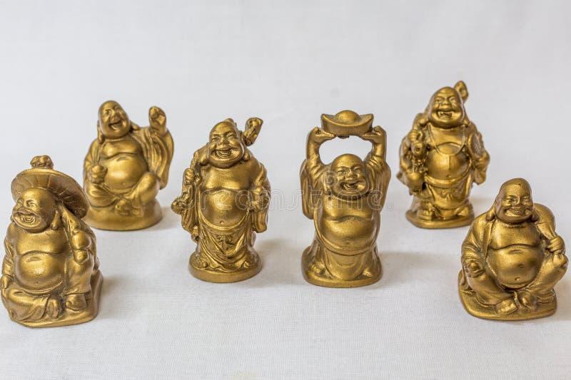 在一个白色背景的金子颜色笑菩萨绘的小组 与极端浅景深的宏指令 库存图片