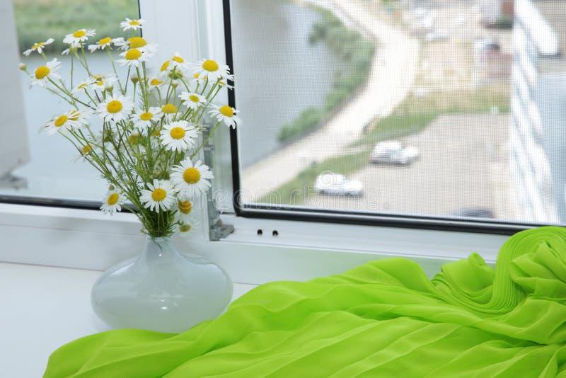在一个白色花瓶的白花在与鲜绿色的织品的白色窗台和与的一个开放白色窗口和街道视图劈裂 免版税图库摄影