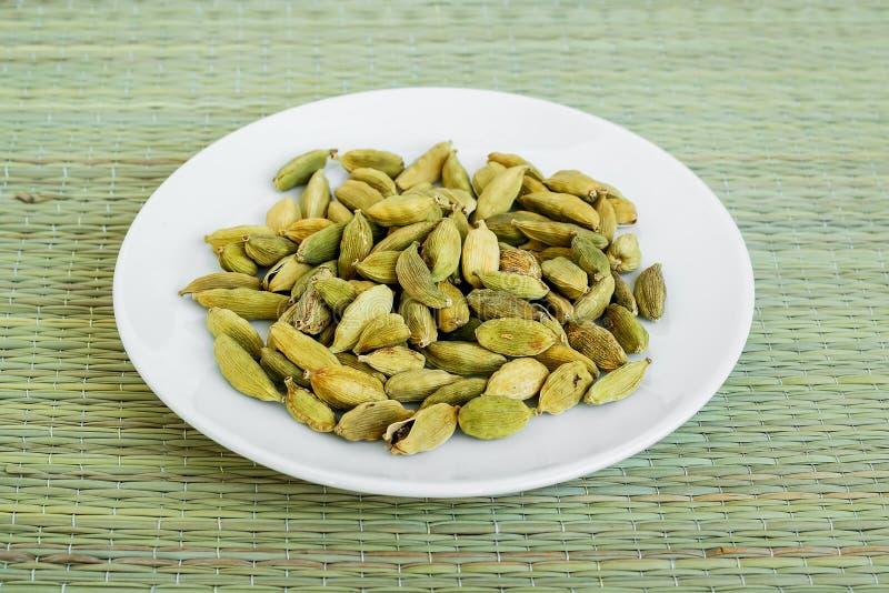 在一个白色茶碟的很多干燥豆蔻果实种子在一张选材台席子由自然植物纤维做成 自然食物香料和 免版税库存图片