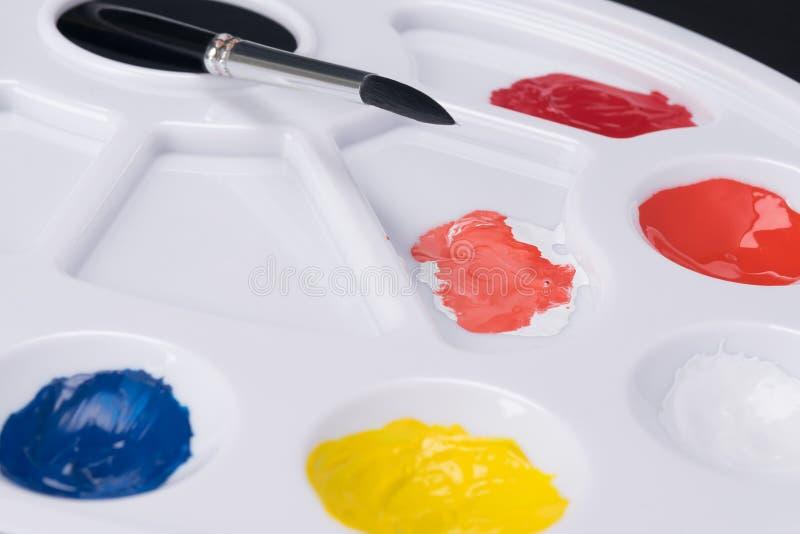 在一个白色调色板的被稀释的多彩多姿的油漆,特写镜头 免版税库存照片