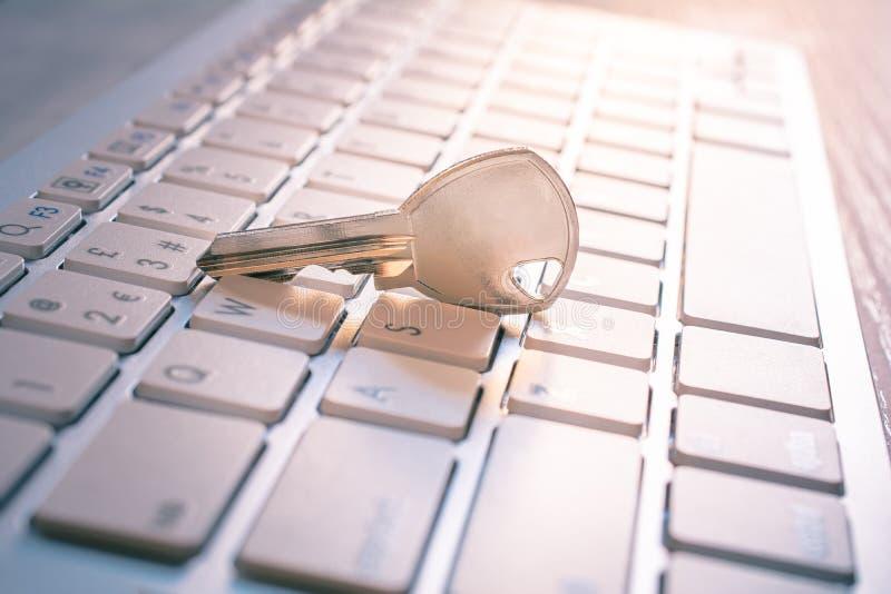 在一个白色键盘的金属钥匙-获取计算机注册概念 免版税库存照片