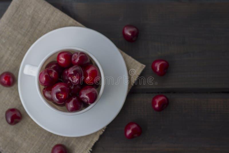 在一个白色陶瓷杯子的新鲜的有机成熟甜樱桃 免版税图库摄影
