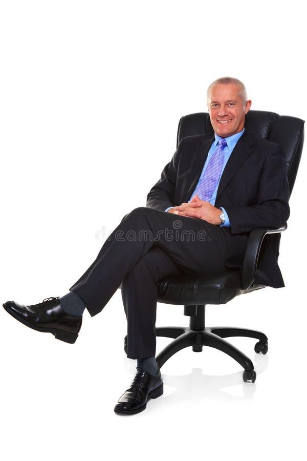 在一个皮椅坐的生意人。 免版税库存图片
