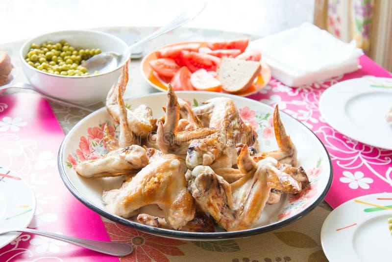 在一个盘、新鲜的蕃茄和罐装绿豆的烤鸡翅在桌上 免版税库存图片