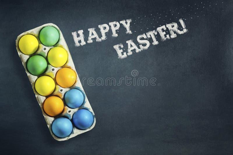 在一个盘子的多彩多姿的复活节彩蛋在深蓝背景 在白垩的题字,复活节快乐 复制空间 复活节 图库摄影
