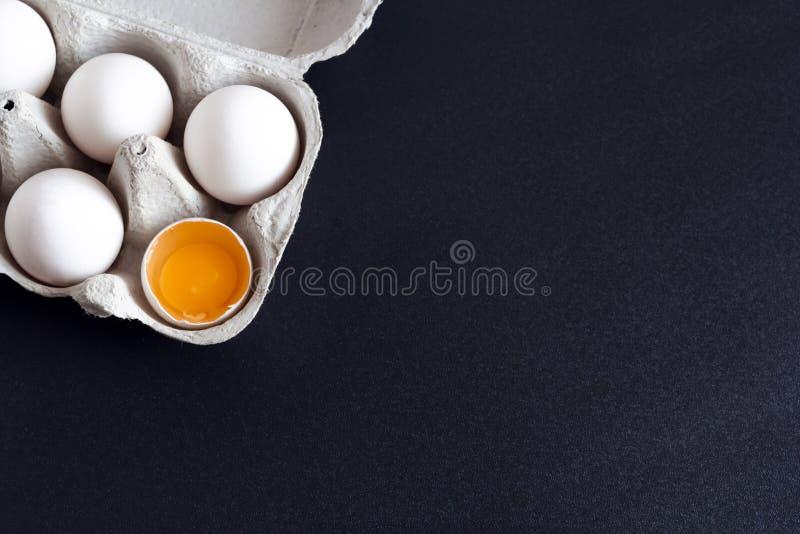 在一个盘子的鸡鸡蛋用一个残破的鸡蛋 免版税库存图片