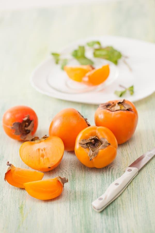 在一个盘的新鲜的成熟柿子在厨房用桌上 免版税图库摄影