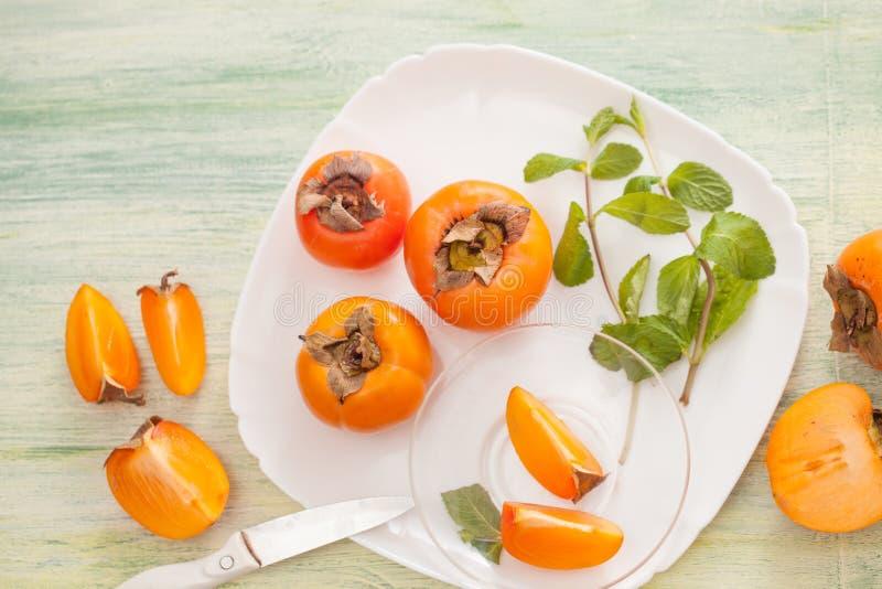 在一个盘的新鲜的成熟柿子在厨房用桌上 免版税库存图片