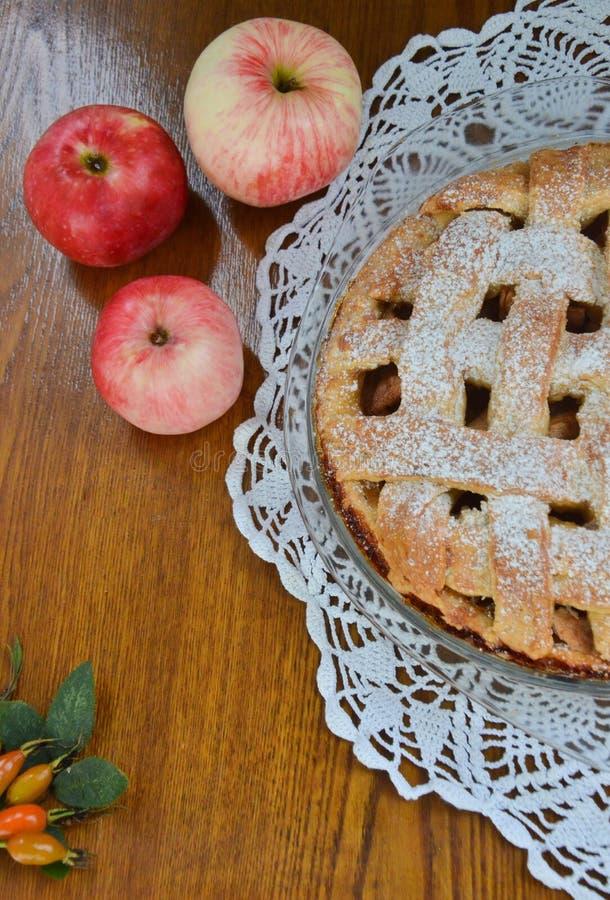 在一个盘的苹果饼在苹果和桌布旁边 库存照片
