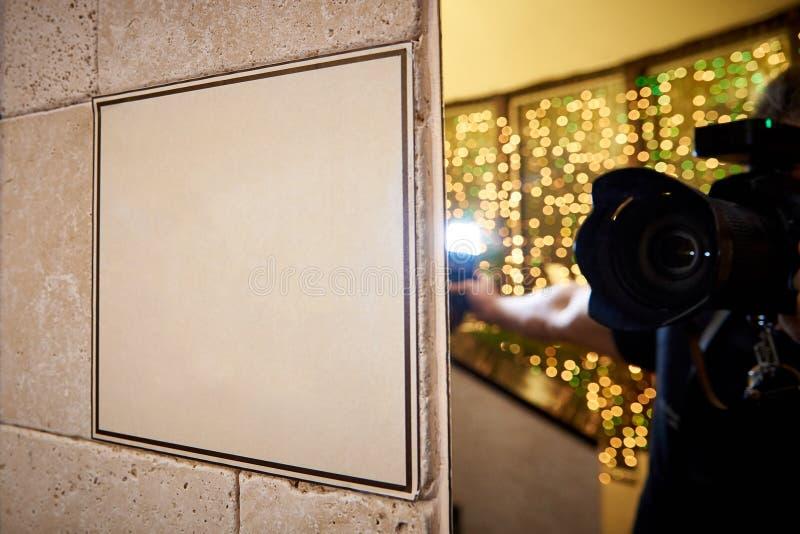 在一个石墙上的牌和摄影师的反射有一台照相机的在镜子 免版税库存图片