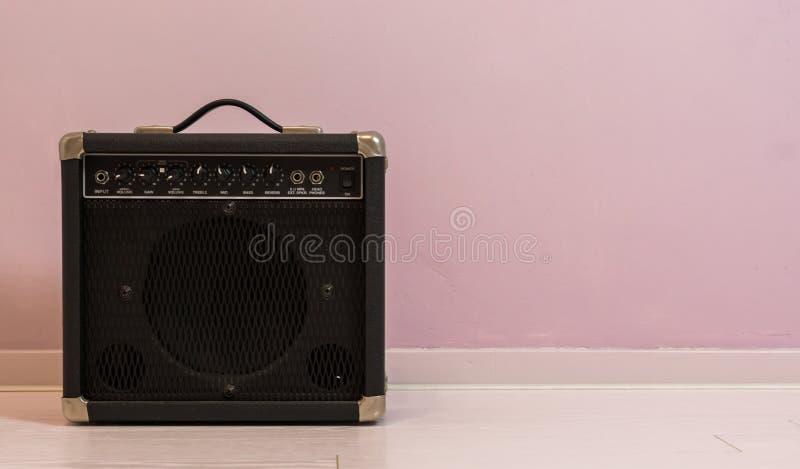 在一个石墙前面被隔绝的便携式的电吉他放大器,音乐设备背景 免版税库存照片