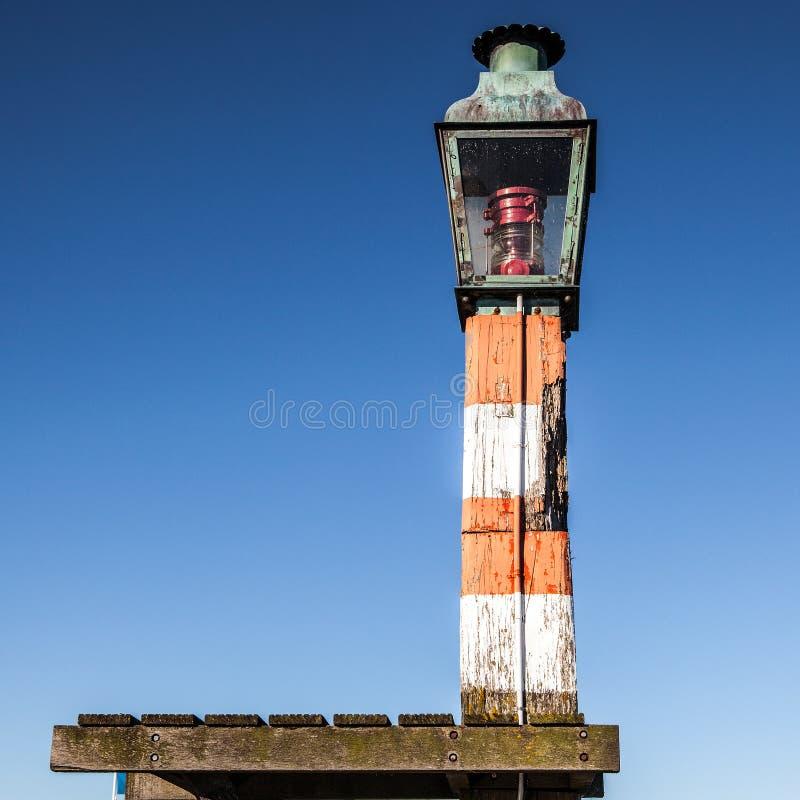 在一个码头的古老沿海灯在福伦丹村庄 库存照片