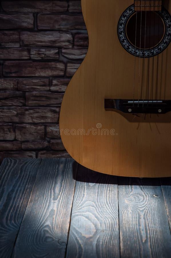 在一个砖墙的背景的声学吉他有光柱的在一张木桌上的 库存照片
