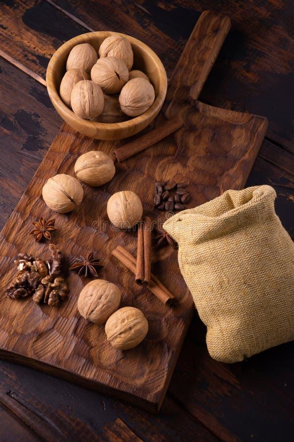 在一个碗、桂香、八角、咖啡豆和小袋子的核桃在木切板 坚果和香料在 免版税库存照片