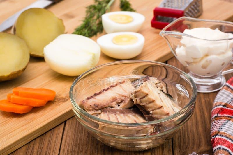 在一个碗和成份的罐装沙丁鱼含羞草沙拉的准备的 库存图片