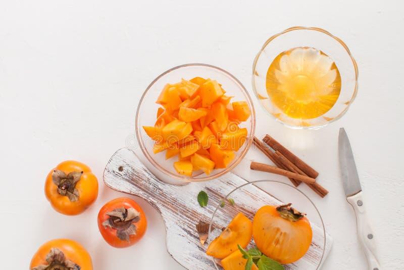 在一个碗的切好的成熟柿子用在白色桌上的肉桂条 库存图片