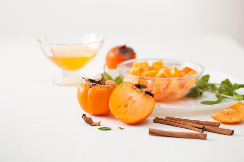 在一个碗的切好的成熟柿子用在白色桌上的肉桂条 免版税库存图片
