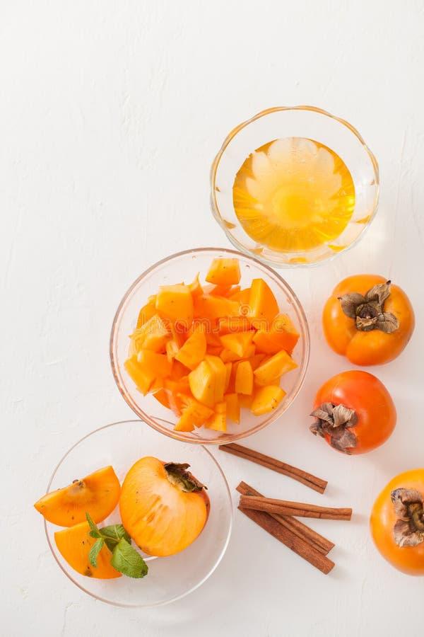 在一个碗的切好的成熟柿子用在白色桌上的肉桂条 免版税图库摄影