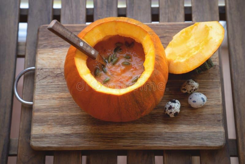 在一个碗的南瓜汤用新鲜的南瓜、大蒜和荷兰芹草本 免版税库存图片