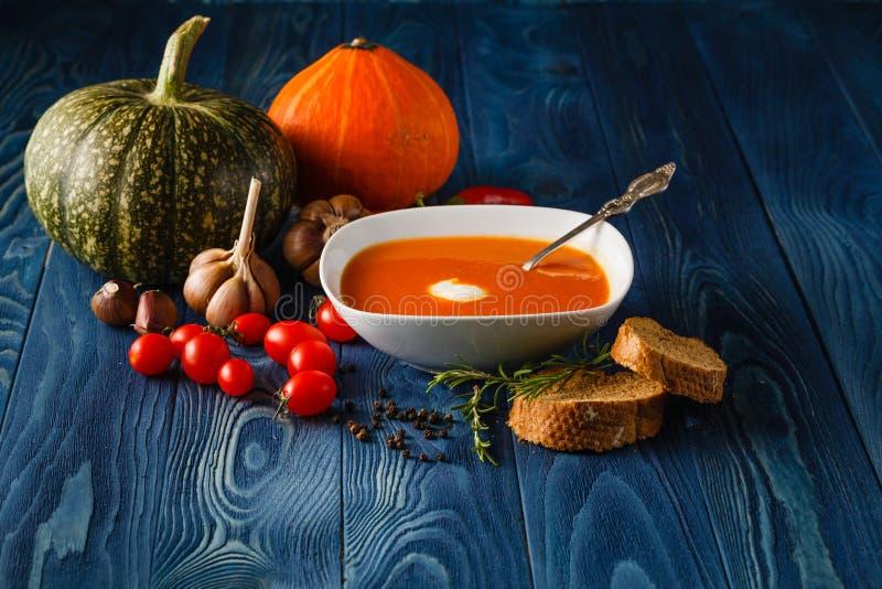 在一个碗的南瓜汤用新鲜的南瓜、大蒜和荷兰芹h 库存照片
