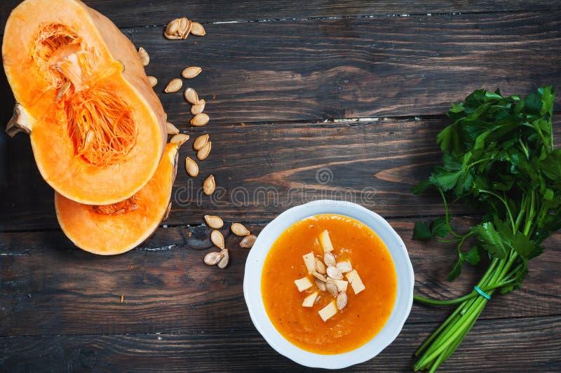在一个碗的南瓜汤用新鲜的南瓜,荷兰芹草本 图库摄影