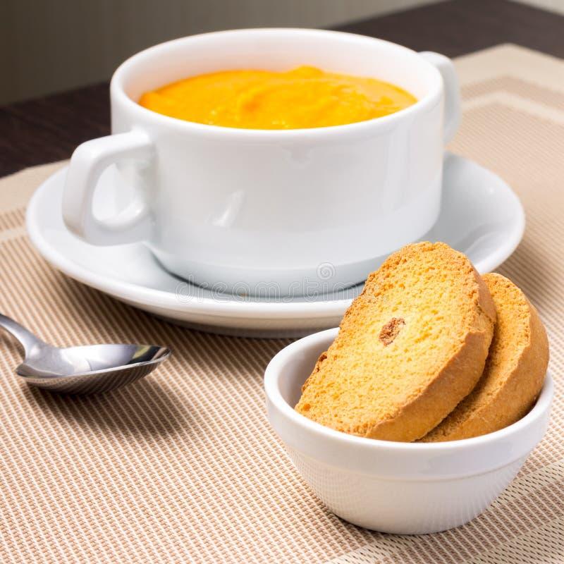 在一个碗的南瓜汤用油煎方型小面包片 库存照片