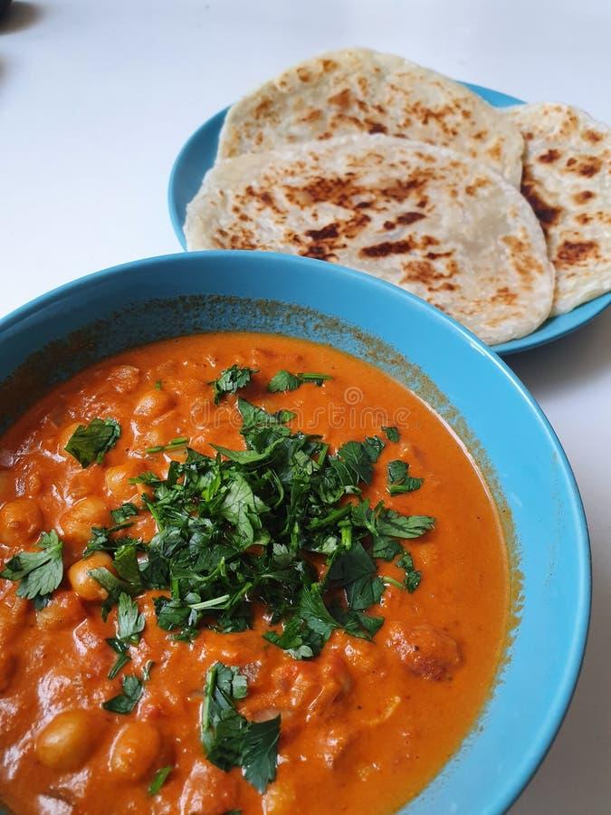 在一个碗的印度咖喱用面包或roti 库存图片