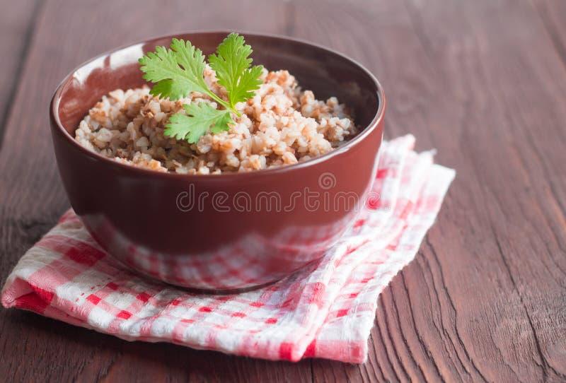 在一个碗的可口荞麦粥在一张木桌上 免版税库存图片