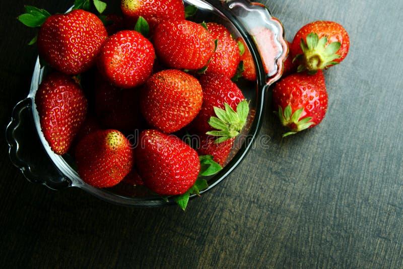 在一个碗的成熟水多和新鲜的草莓在木背景 免版税库存照片