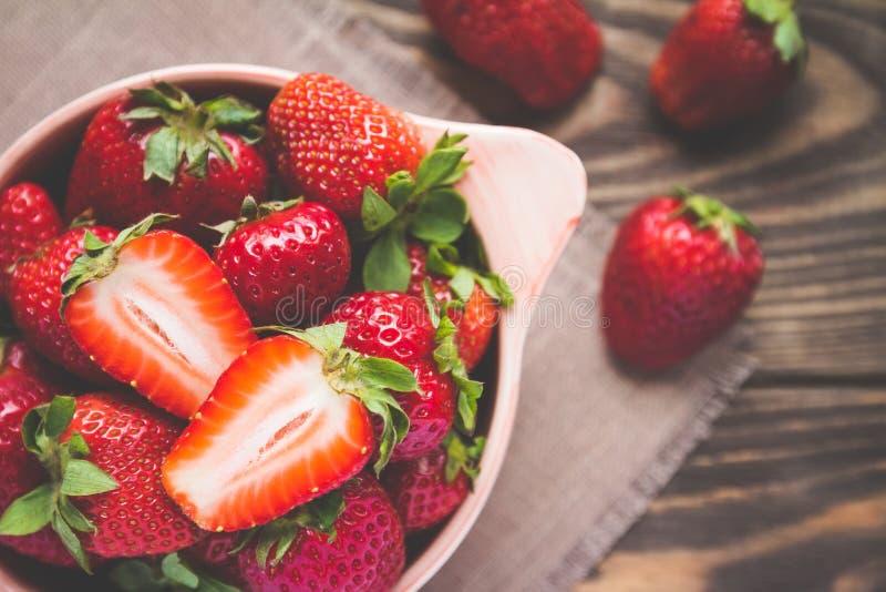 在一个碗的成熟草莓在一张木桌上 免版税库存图片