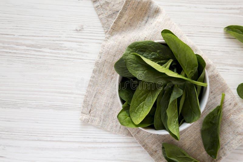 在一个碗的新鲜的未加工的菠菜在白色木背景,顶视图 r r 免版税库存图片