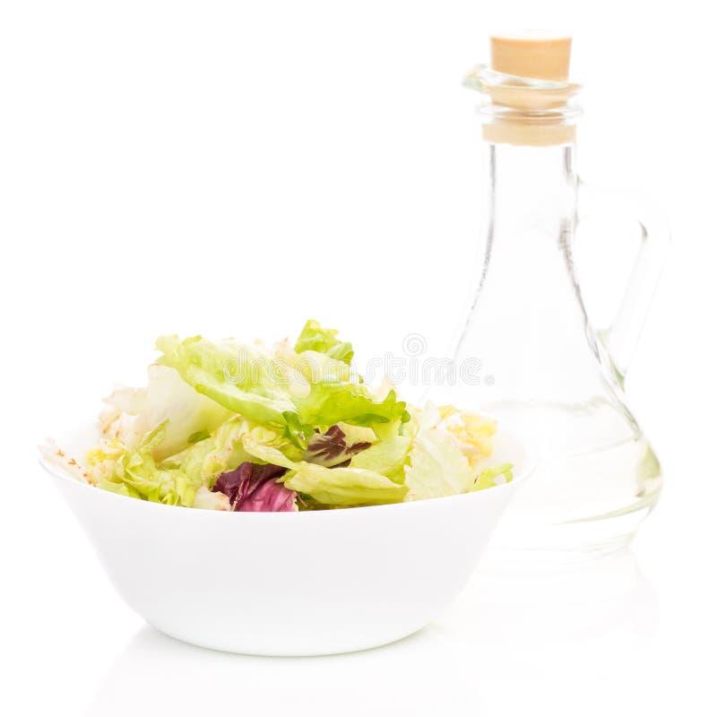 在一个碗的新鲜的沙拉有瓶的油 免版税库存图片