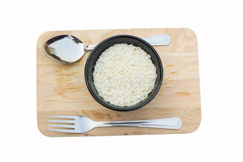 在一个碗的未煮过的米,在斩肉板,与叉子和匙子, 免版税库存图片
