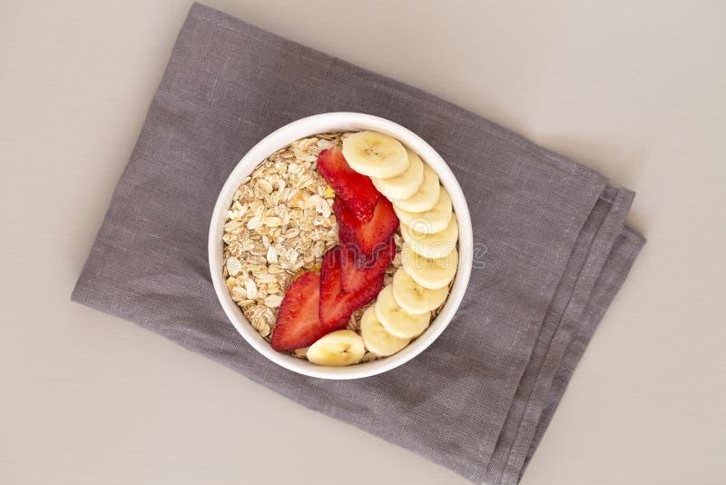 在一个碗的燕麦粥muesli用草莓、香蕉和亚麻籽 r 免版税图库摄影