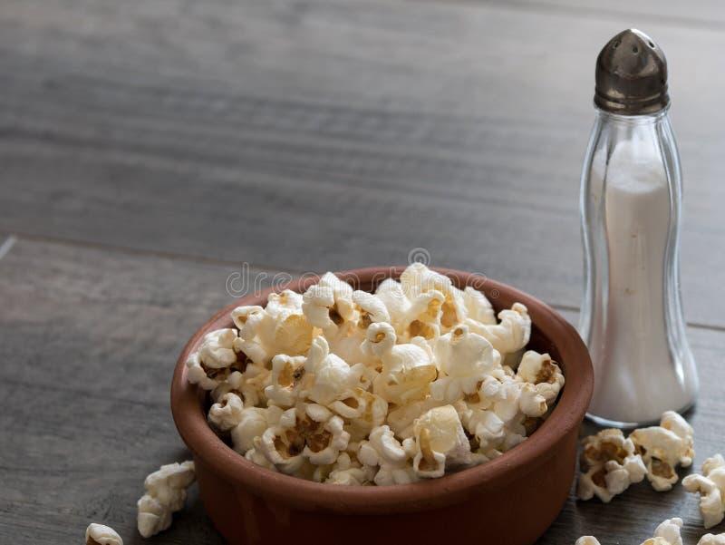 在一个碗的玉米花有在木背景的盐的 库存照片