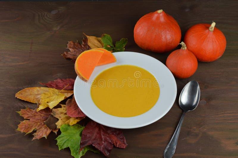 在一个碗的秋季南瓜汤用北海道南瓜、叶子和一把匙子在一张棕色木桌上 库存照片