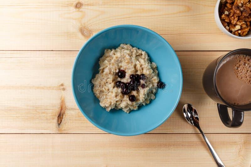 在一个碗的粥用莓果、核桃和可可粉在明亮的木桌上 健康早餐图象 免版税库存照片