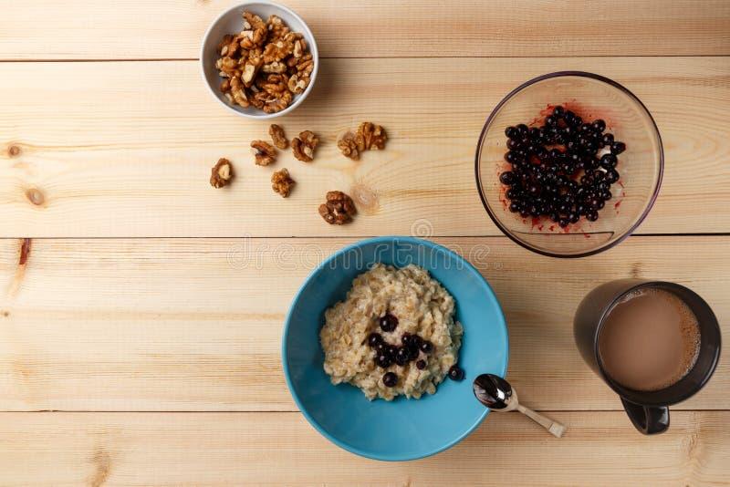 在一个碗的粥用莓果、核桃和可可粉在明亮的木桌上 健康早餐图象 库存照片