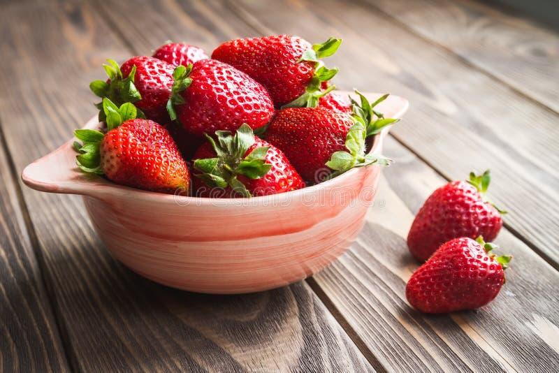 在一个碗的草莓在一张老棕色桌上 图库摄影
