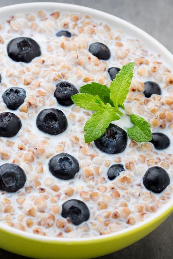 在一个碗的荞麦粥有薄荷叶和蓝莓的 库存图片