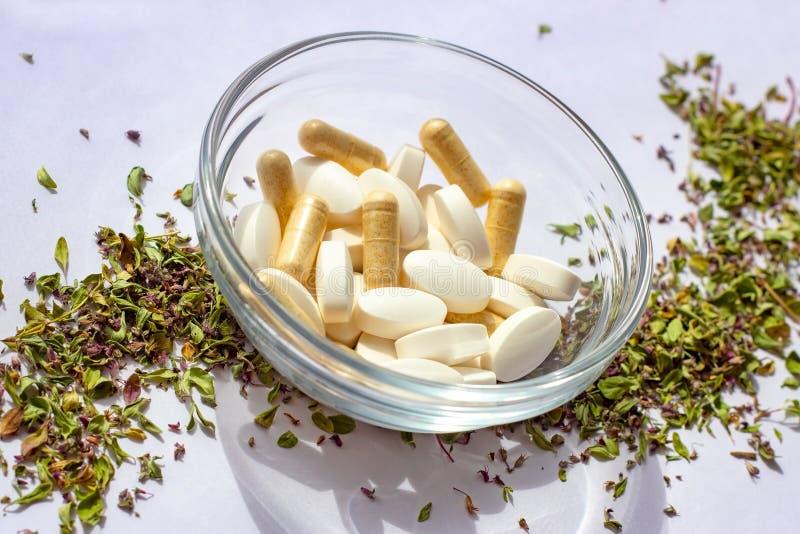 在一个碗的营养补充药片在干草本背景 r 免版税库存照片