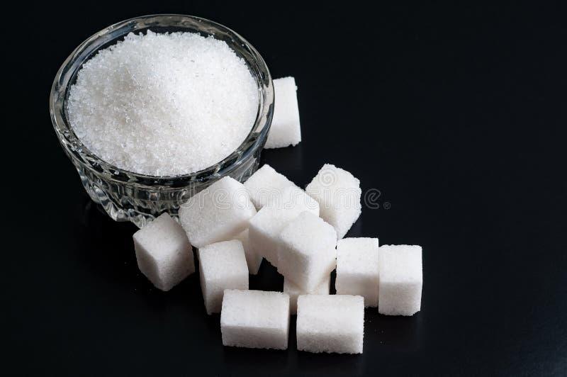 在一个碗的顶视图用在bl的白色被颗粒化的和精制糖 免版税图库摄影
