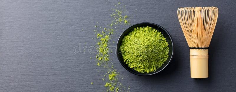 在一个碗的Matcha绿茶烹饪过程有竹子的扫 背景黑色板岩 复制空间 顶视图 免版税库存图片