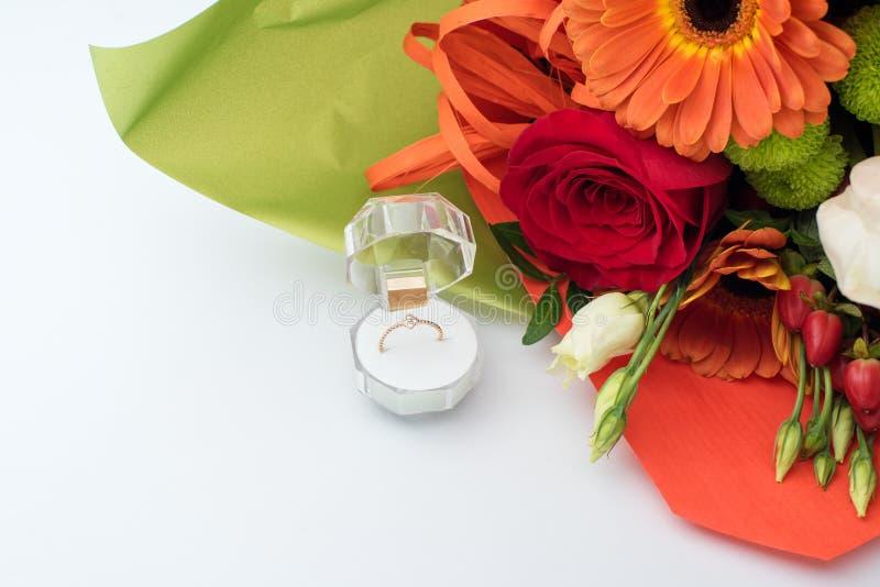 在一个礼物盒的定婚戒指有花明亮的花束的  结婚的提议 礼物为圣华伦泰` s天 库存图片
