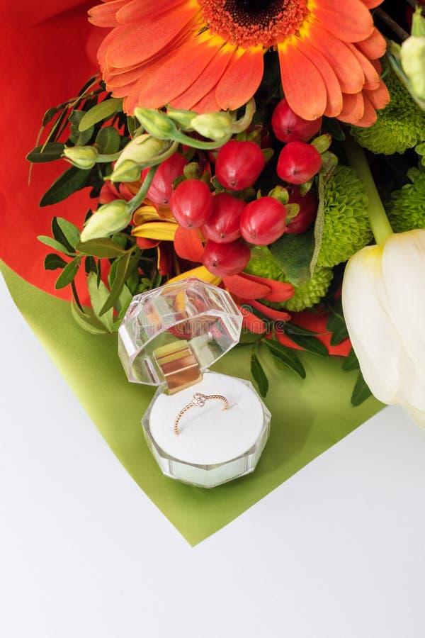 在一个礼物盒的定婚戒指有花明亮的花束的  结婚的提议 礼物为圣华伦泰` s天 免版税库存图片
